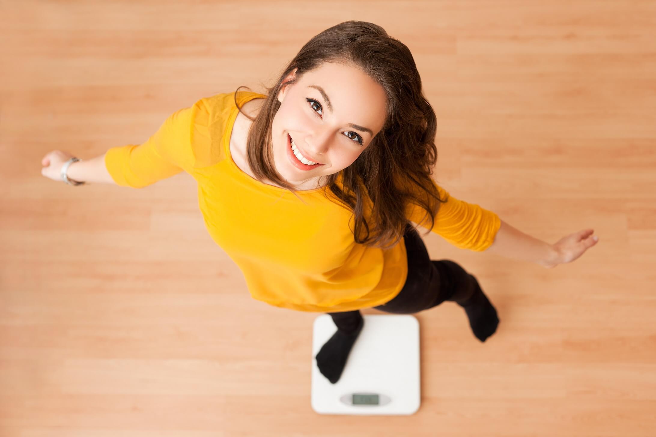 Abnehmen ohne Diät Frau ist glücklich über Erfolg auf Waage
