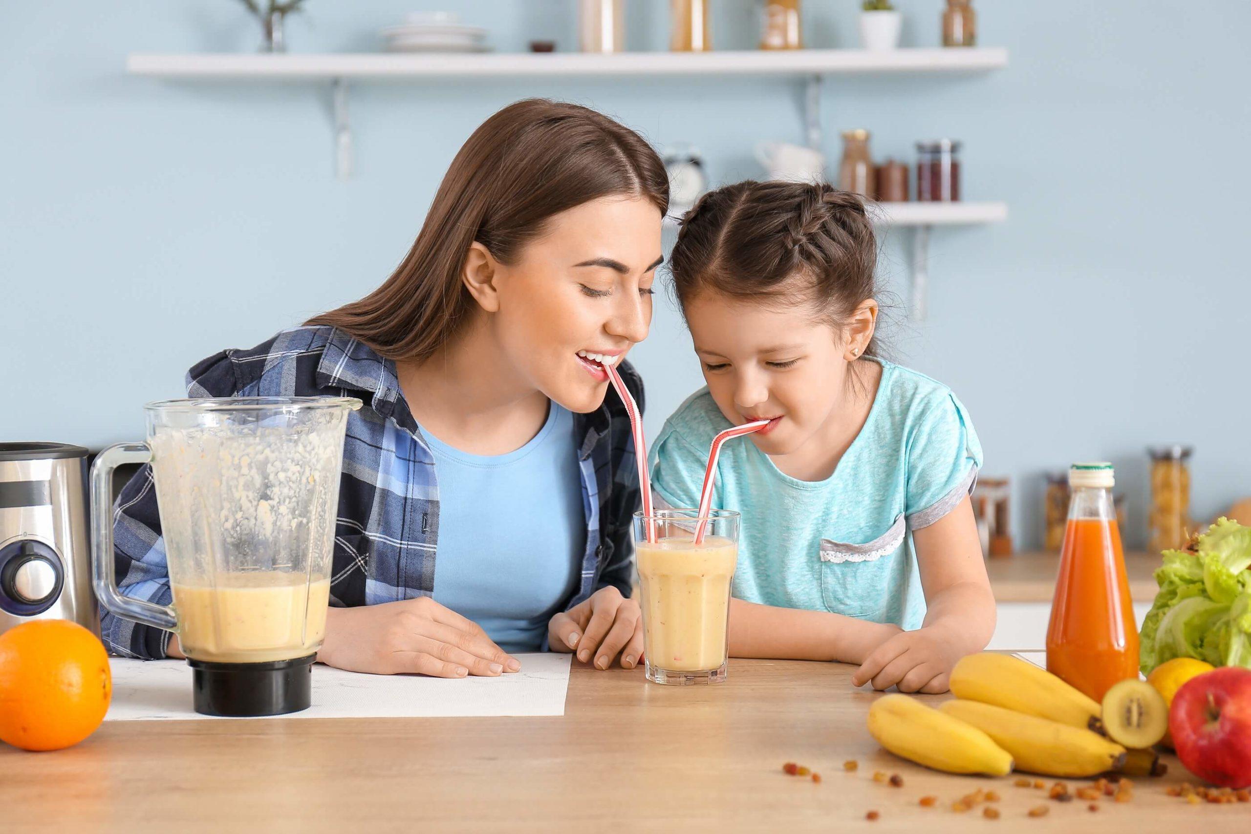 Mutter-und-Kind-trinken-zubereiteten-gesunden-Smoothie